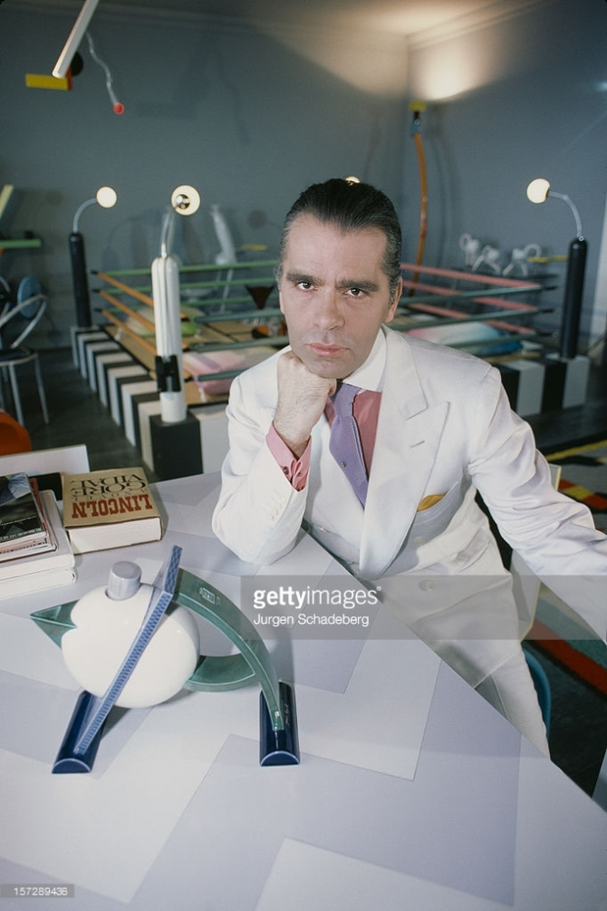 German fashion designer Karl Lagerfeld poses with a teapot from his Memphis collection, and the new novel 'Lincoln' by Gore Vidal, 1984. CREDIT: JURGEN SCHADEBERG