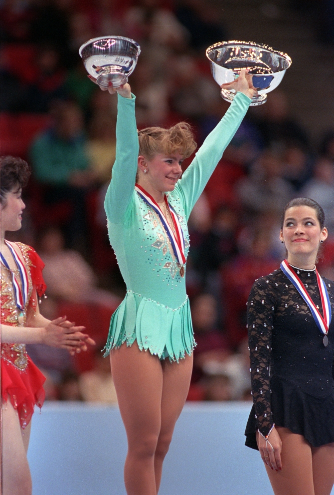 Tonya Harding of Portland, Ore., raises her trophies after winning the U.S. Figure Skating Championship in Minneapolis, Minn., on Saturday, Feb. 16, 1991. Harding became the first American woman to successfully complete a triple axel in competition at the event. At left is Kristi Yamaguchi, with third place Nancy Kerrigan at right. (AP Photo/Larry Salzman)